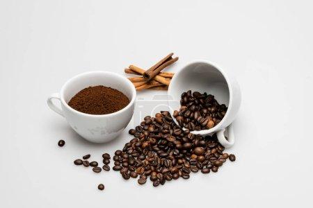 bâtons de cannelle près des tasses avec du café moulu et des haricots sur blanc