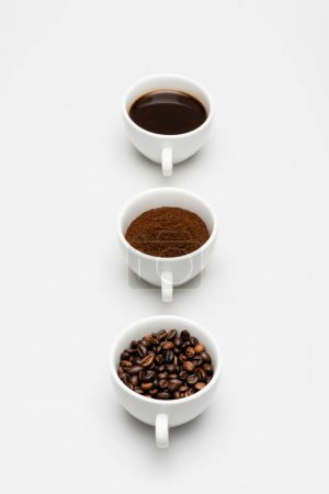 Tassen mit Bohnen, zubereiteten und gemahlenen Kaffee auf weiß