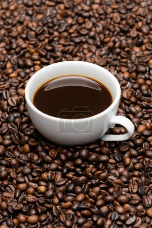 white cup with prepared coffee on brown beans