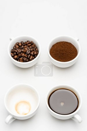top view of prepared americano near ground coffee and beans in cups on white