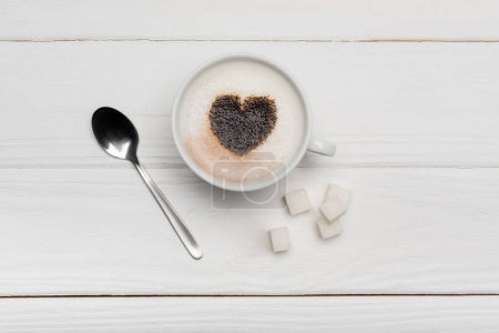 Photo for Top view of cup with cappuccino near spoon and sugar cubes on white wooden background - Royalty Free Image