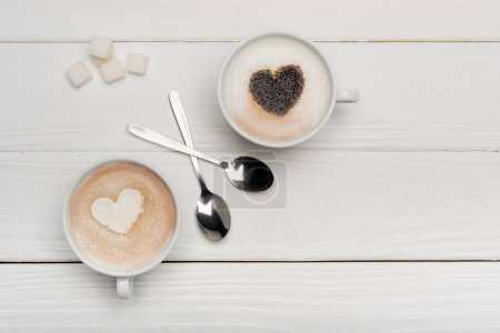 top view of cups with cappuccino and latte near spoons and sugar cubes on white wooden background