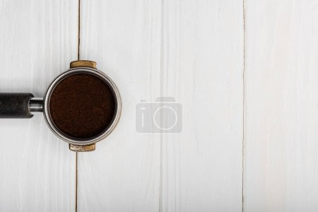 top view of metallic portafilter with fresh ground coffee on white wooden surface