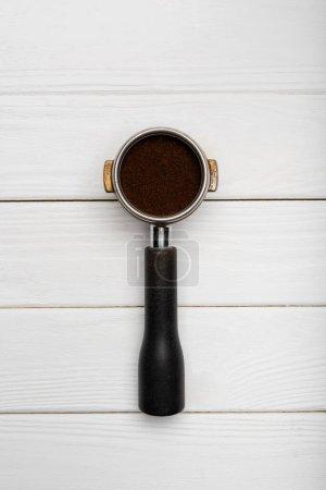 vue de dessus du portafilter métallique avec café moulu frais sur blanc