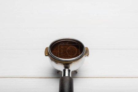 metallic portafilter with ground coffee on white surface