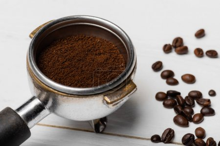 close up of metallic portafilter with ground coffee near beans on white