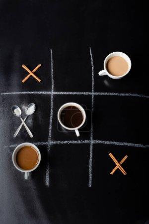 Tic Tac Toe Spiel mit Löffeln, Zimtstangen und Tassen Kaffee auf schwarz