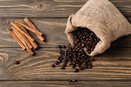 vue du dessus du sac à dos avec grains de café torréfiés près des bâtons de cannelle sur la surface en bois