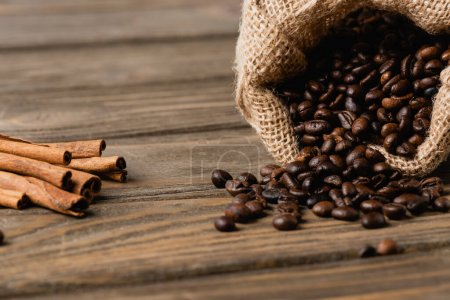 sack bag with roasted coffee beans near cinnamon sticks on blurred wooden surface