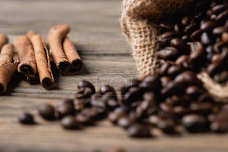 bâtons de cannelle près sac à dos avec grains de café torréfiés sur une surface en bois floue