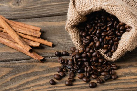 cinnamon sticks near sack bag with roasted coffee beans on wooden surface
