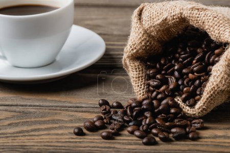 sack bag with roasted coffee beans near cup on wooden surface