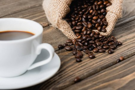 sack bag with roasted coffee beans near blurred cup on wooden surface