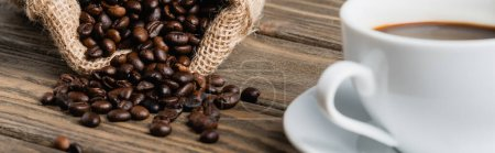 Säckebeutel mit gerösteten Kaffeebohnen in der Nähe einer verschwommenen Tasse auf Holzoberfläche, Banner