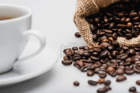 sack bag with roasted coffee beans near cup on blurred foreground