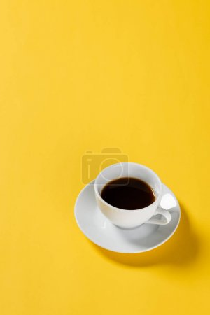high angle view of black coffee in white cup on yellow background