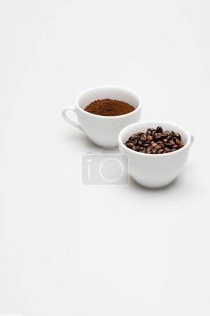 Photo pour Grains et café moulu dans des tasses sur blanc - image libre de droit