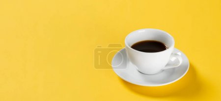 black coffee in white cup on yellow background, banner