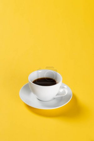 black coffee in white mug on yellow background