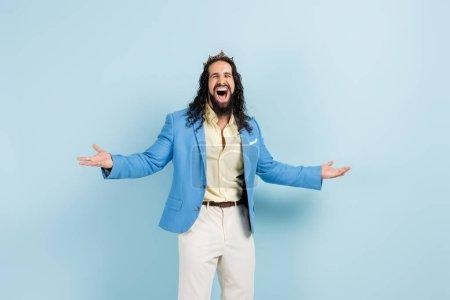 aufgeregter hispanischer Mann in Krone und Jacke mit ausgestreckten Händen auf blauem Grund stehend