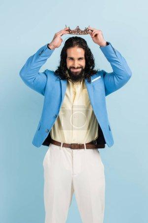 Photo pour Homme hispanique barbu en veste avec couronne et sourire isolé sur bleu - image libre de droit