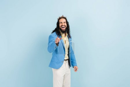 bearded hispanic man in crown and jacket laughing while pointing with finger on blue