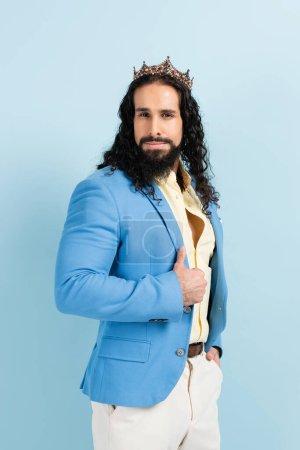 bärtiger hispanischer Mann in Krone und Jacke posiert isoliert auf blauem Grund