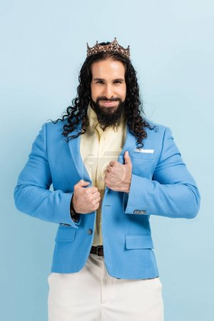 Photo for Cheerful hispanic man in crown adjusting jacket isolated on blue - Royalty Free Image
