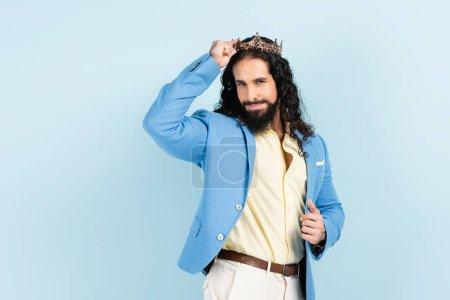 hombre hispano barbudo y rizado en chaqueta ajustando corona aislado en azul