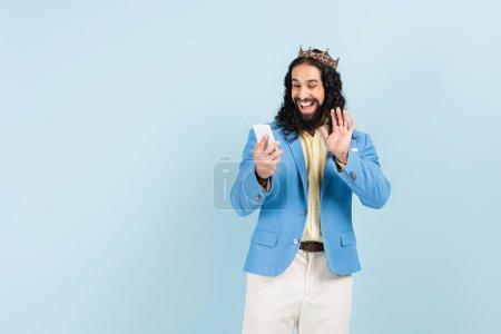 bärtiger hispanischer Mann in Jacke und Krone winkt bei Videoanruf isoliert auf blau