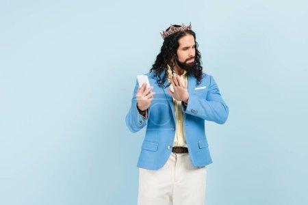 Photo pour Offensé homme hispanique en veste et couronne montrant geste d'arrêt tout en tenant smartphone isolé sur bleu - image libre de droit