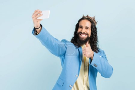 happy hispanic man in jacket and crown showing thumb up and taking selfie isolated on blue