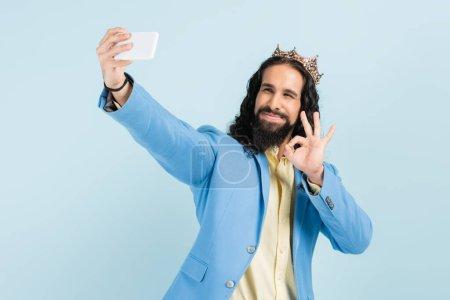 glücklich hispanische Mann in Jacke und Krone zeigt okay und macht Selfie isoliert auf blau