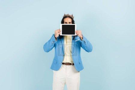 Spanisch Mann in Jacke und Krone hält digitale Tablette mit leerem Bildschirm isoliert auf blau