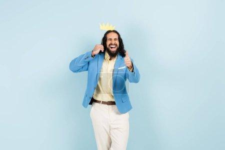 hombre hispano feliz en chaqueta sosteniendo la corona de papel en palo y mostrando el pulgar hacia arriba aislado en azul