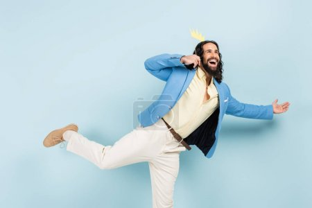 happy hispanic man in jacket holding paper crown on stick and gesturing on blue