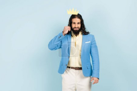 displeased hispanic man in jacket holding paper crown on stick isolated on blue
