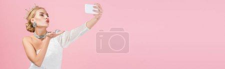 Photo for Blonde woman in luxury crown taking selfie on smartphone and sending air kiss isolated on pink, banner - Royalty Free Image