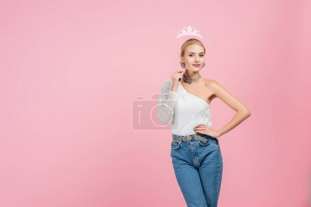stylish woman holding paper crown on stick and standing with hand on hip isolated on pink