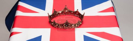 golden royal crown on british flag isolated on grey, banner