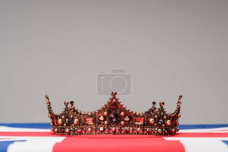 golden royal crown on british flag isolated on grey
