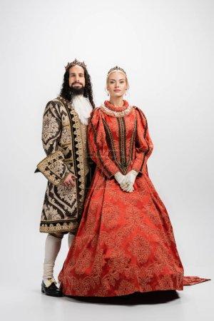 Photo pour Longueur totale du couple interracial historique en couronnes d'or et vêtements médiévaux sur blanc - image libre de droit