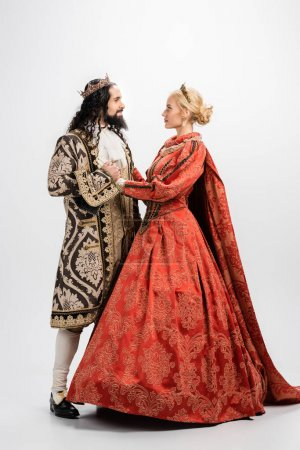 full length of historical interracial couple in crowns and medieval clothing looking at each other on white