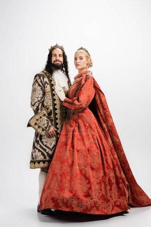 Photo pour Longueur totale de couple interracial historique en couronnes et vêtements médiévaux debout sur blanc - image libre de droit