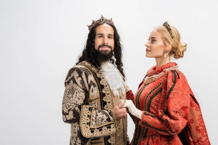 Photo for Historical interracial couple in crowns and medieval clothing holding hands isolated on white - Royalty Free Image
