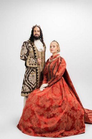 full length of historical interracial couple in crowns on white