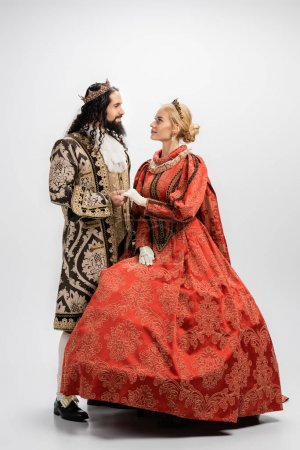 full length of historical interracial couple in crowns and medieval clothing looking at each other and holding hands on white