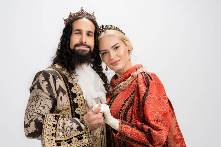 happy historical interracial couple in crowns and medieval clothing isolated on white