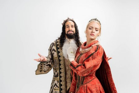 hispanic king in crown and medieval clothing looking at blonde wife showing no gesture isolated on white