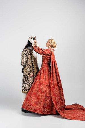 Photo pour Pleine longueur de reine blonde en robe portant la couronne sur roi hispanique en vêtements médiévaux sur blanc - image libre de droit